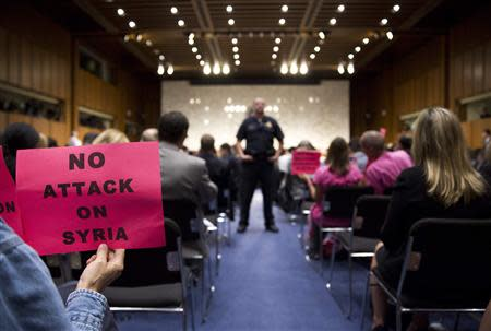 A protester holds up a sign against U.S. action in Syria as Chairman of the Joint Chiefs General Martin E. Dempsey, John Kerry, U.S. Secretary of State, and Chuck Hagel, Secretary of Defense, present the administration's case for U.S. military action against Syria to a Senate Foreign Relations Committee hearing in Washington September 3, 2013. REUTERS/Joshua Roberts