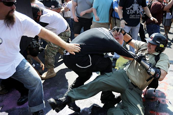 <p>White nationalists, neo-Nazis and members of the 'alt-right' clash with counter-protesters as they enter Lee Park during the 'Unite the Right' rally August 12, 2017 in Charlottesville, Virginia. After clashes with anti-fascist protesters and police the rally was declared an unlawful gathering and people were forced out of Lee Park, where a statue of Confederate General Robert E. Lee is slated to be removed. (Photo: Chip Somodevilla/Getty Images) </p>