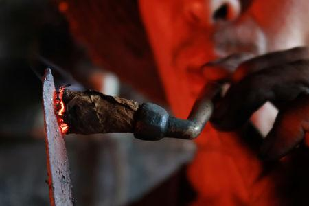 A blacksmith lights his pipe with a heated iron stick at a workshop for handmade woks in Datian village, Hubei province, China August 13, 2018. Picture taken August 13, 2018. REUTERS/Thomas Suen