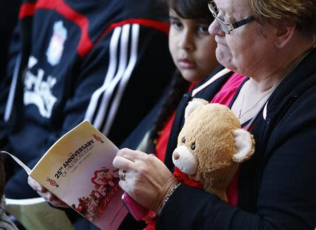 A woman reads a programme during a memorial service to mark the 25th anniversary of the Hillsborough disaster at Anfield in Liverpool, northern England April 15, 2014. REUTERS/Darren Staples
