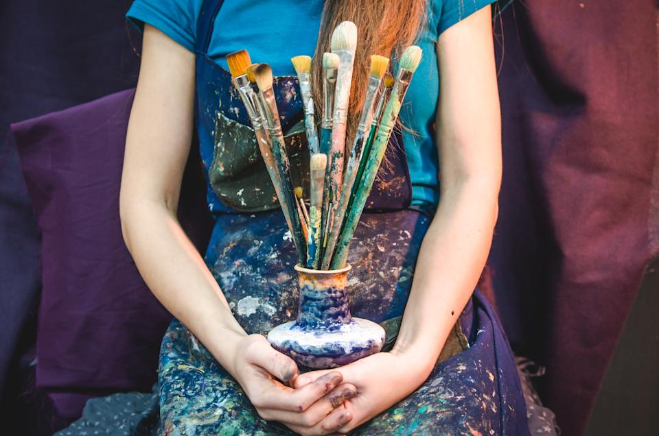 Female artist holding a bunch of brushes. Creativity and imagination concept