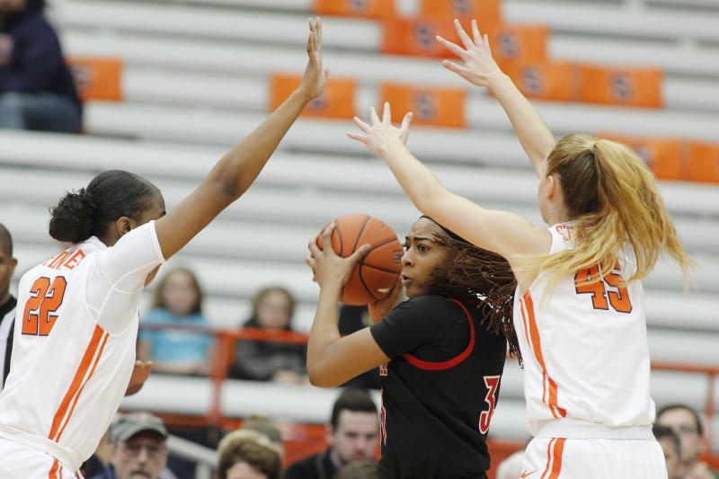 Louisville's Bionca Dunham, center, tries the pass the ball while guarded by Syracuse's Amaya Finklea-Guity, left, and Digna Strautmane, right, in the first quarter of an NCAA college basketball game in Syracuse, N.Y., Sunday, Feb. 9, 2020. (AP Photo/Nick Lisi)