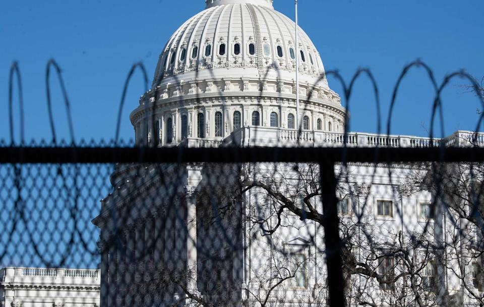 <p>Barbed wire is installed on the top of a security fence surrounding the US Capitol ahead of next week's inauguration</p> (AFP via Getty Images)