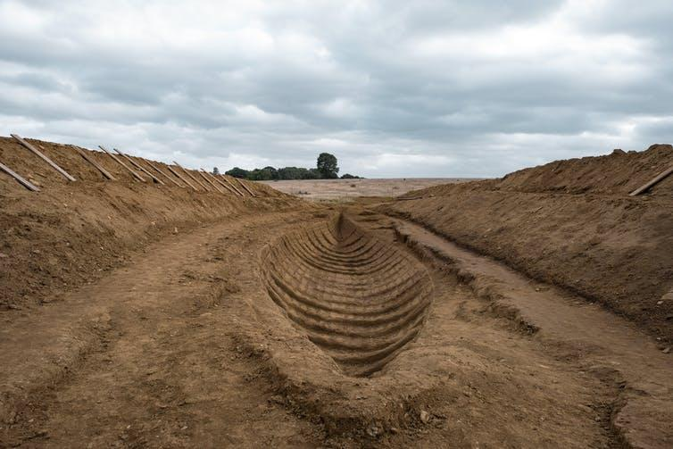 Wide trench containing the imprint of a wooden ship in the soil.