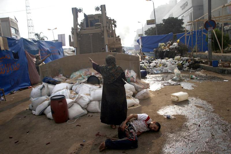 A file picture taken on August 14, 2013 shows an Egyptian woman trying to stop a military bulldozer from hurting a wounded youth during clashes that broke out as Egyptian security forces moved in to disperse supporters of Egypt's Mohamed Morsi (AFP Photo/Mohammed Abdel Moneim)