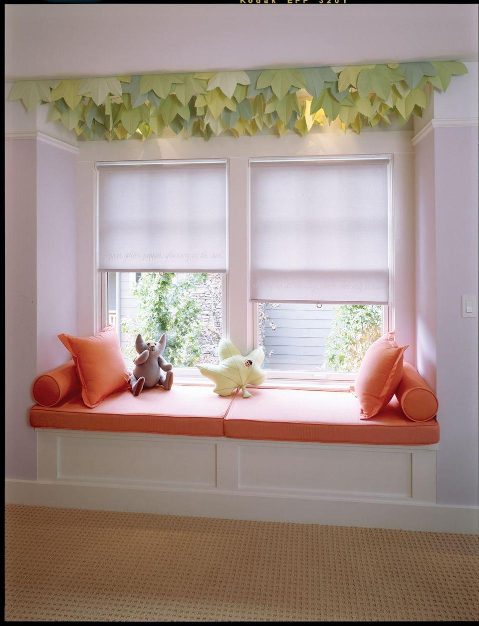 <p>From a ceiling boasting playful leaf decor to an energetic orange bench cushion, any kid would appreciate this reading nook. </p>