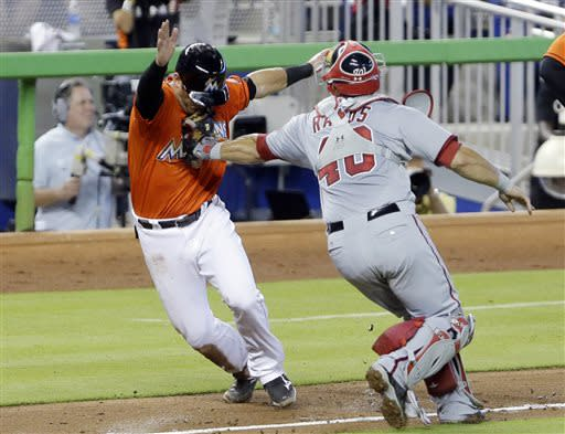 Miami Marlins' Jeff Mathis is tagged by Washington Nationals catcher Wilson Ramos after Mathis was caught between third base and home plate during the third inning of a baseball game, Sunday, July 14, 2013 in Miami. (AP Photo/Wilfredo Lee)