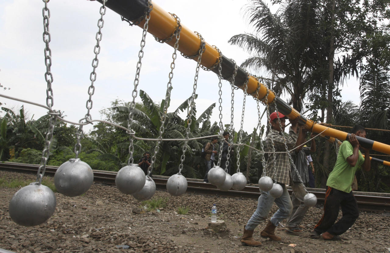 Workers install a frame with concrete balls suspended on it above railway tracks in Bekasi, West Java, Indonesia, Tuesday, Jan. 17, 2012. Indonesia has gone to imaginative extremes to try to stop commuters from riding the roofs of trains by suspending rows of grapefruit-sized concrete balls above railway lines a few inches (centimeters) above the tops of carriages at points where trains enter or pull out of stations, or where they go through crossings. (AP Photo/Achmad Ibrahim)