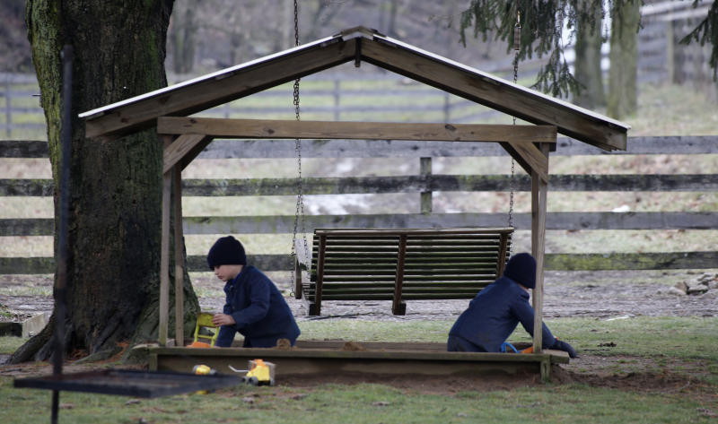 In this photo made on Tuesday, Jan. 29, 2013, a pair of young Amish boys play in a sandbox in front of the home of Sam Mullet Sr., in Bergholz, Ohio. Mullet is one of sixteen men and women facing sentencing Friday, Feb. 8, 2013 in beard-cutting attacks on fellow Amish in Ohio. The defendants want leniency so they can return to their homes and farms, to teach their sons a trade and their daughters how to sew, cook and keep house. (AP Photo/Keith Srakocic)