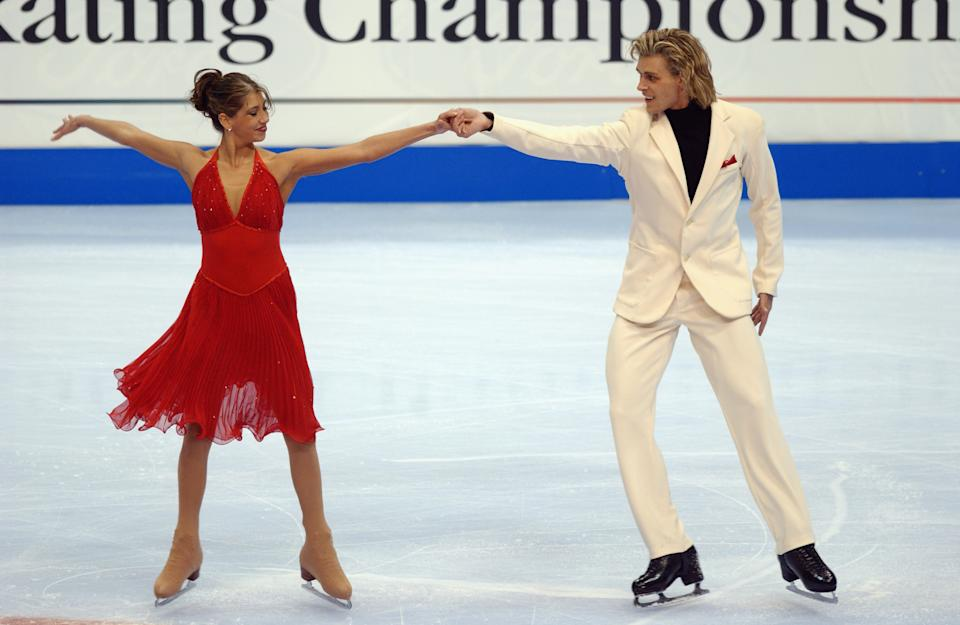 Peter Tchernyshev and Naomi Lang hold hands and face the camera during their competition. She is wearing a red, flowing dress while he is wearing a white suit.