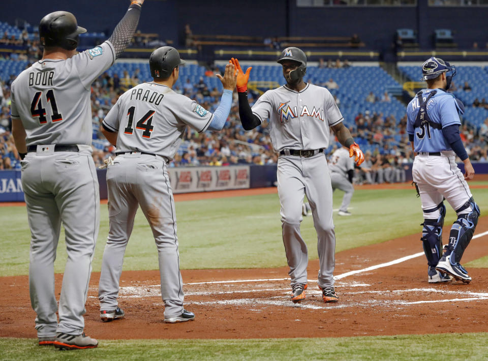 Miami Marlins' Justin Bour (41) and Martin Prado (14) celebrate with Cameron Maybin after all three scored behind Tampa Bay Rays catcher Adam Moore during the second inning of a baseball game Sunday, July 22, 2018, in St. Petersburg, Fla. (AP Photo/Mike Carlson)