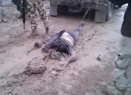 A still image made from undated footage posted on the YouTube social media website and believed to be shot in Anbar province shows a dead man, suspected of being a member of the al Qaeda-linked Islamic State in Iraq and the Levant (ISIL) group, tied to the back of an Iraqi military vehicle before the vehicle is driven away, as men in Iraqi military uniforms stand close by. REUTERS/YouTube