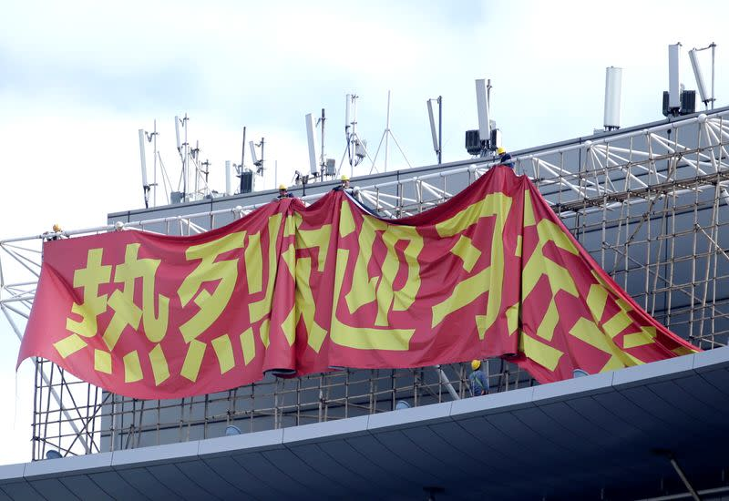 Workers hang up a giant banner on the roof of a building next to Macau Tower, welcoming Chinese President Xi Jinping to visit Macau, ahead of the 20th anniversary of the former Portuguese colony's return to China, in Macau