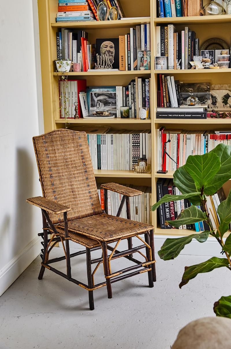 A French rattan chair is positioned within arm's reach of a built-in double bookcase.