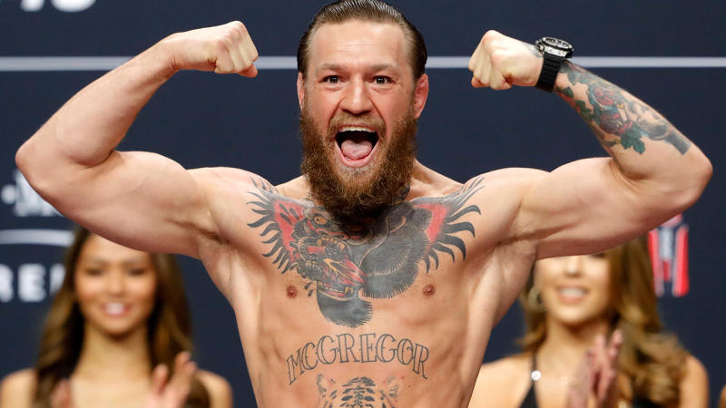 Irishman Conor McGregor smiles and poses on the scale ahead of the Donald Cerrone fight.