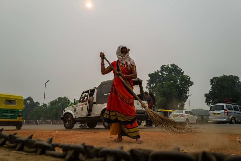 A woman sweeps a street near India Gate under heavy smog in New Delhi on Oct. 29, 2019. Photo: Jewel Samad/AFP via Getty Images)