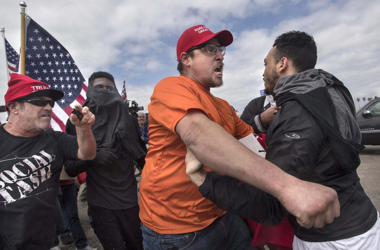 """<p>A supporter of President Donald Trump, center, clashes with an anti-Trump protester in Huntington Beach, Calif., on Saturday, March 25, 2017. Counter-protesters said before the march began that they planned to try to stop the march's progress with a """"human wall."""" (Mindy Schauer/The Orange County Register via AP) </p>"""