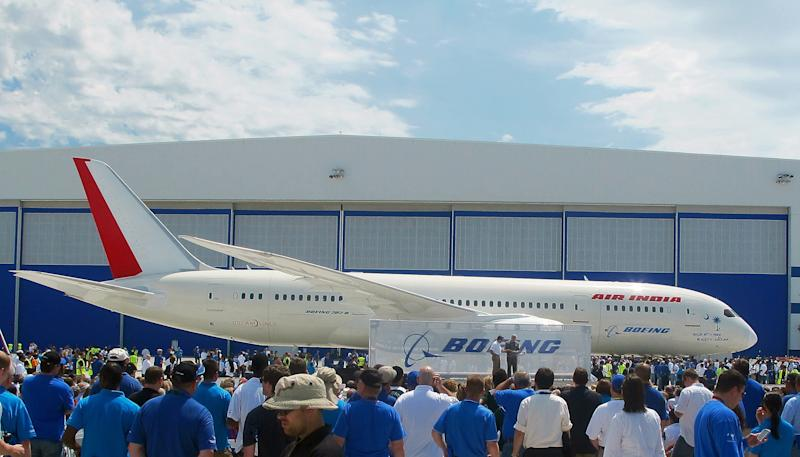 Boeing workers work gather around a 787 at the company's assembly plant in North Charleston, S.C., on Friday, April 27, 2012. The plane, rolled out Friday, is the first 787 manufactured at the company's South Carolina plant that opened last year. (AP Photo/Bruce Smith)