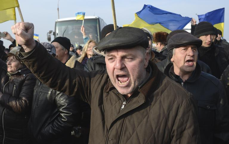 Ukrainians carrying their country's flags stage a protest at the Chongar check point blocking the entrance to Crimea on March 7, 2014