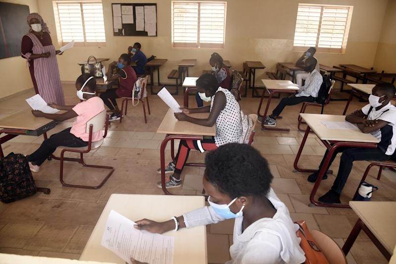 TOPSHOT - Pupils wearing face masks are seen in class in Dakar on June 25, 2020, on the opening day of the classes for the students in the examination class in Senegal. - Schools have been closed since early March 2020 due to the outbreak of the COVID-19 coronavirus in Senegal. (Photo by Seyllou / AFP) (Photo by SEYLLOU/AFP via Getty Images)