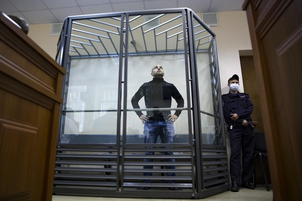 """Andrei Pivovarov, head of the Open Russia movement, stands in a glass enclosure during a court session in Krasnodar, Russia, on Wednesday, June 2, 2021. The court sent the prominent opposition activist to jail pending a probe, as authorities continue to crack down on dissent ahead of September's parliamentary election. Pivovarov was pulled off a Warsaw-bound plane at St. Petersburg's airport just before takeoff late Monday and taken to Krasnodar, where authorities accused him of supporting a local election candidate last year on behalf of an """"undesirable"""" organization. (AP Photo)"""