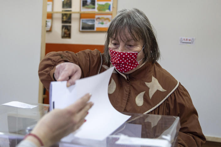 A woman casts her ballot during parliamentary elections in the town of during the parliamentary elections in the town of Bankya, Bulgaria, Sunday, April 4, 2021. Bulgarians are heading to the polls on Sunday to cast ballots for a new parliament after months of anti-government protests and amid a surge of coronavirus infections. (AP Photo/Visar Kryeziu)