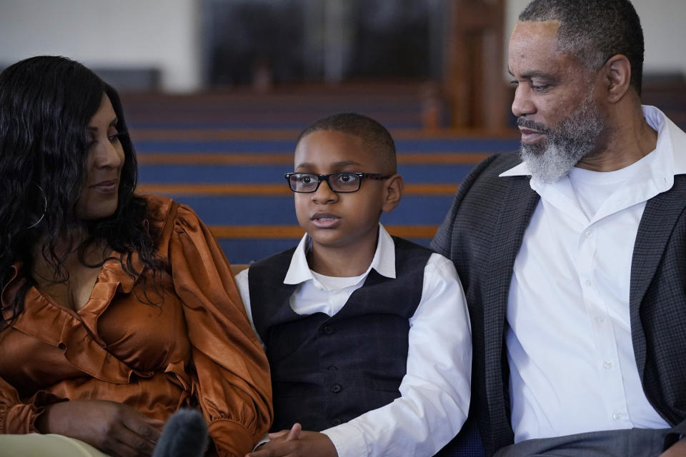 """LeRoy """"Tripp"""" Gibbs III, center, 12-year-old great-grandson of Tulsa Race Massacre survivor Ernestine Alpha Gibbs, speaks during an interview with family members in Tulsa, Okla., on Sunday, April 11, 2021. With him are his parents, Tracy and LeRoy Gibbs II. LeRoy II credits his grandmother, who not only built wealth and passed it on, but also showed succeeding generations how it was done. It was a lesson that few descendants of the victims of the race massacre had an opportunity to learn. """"The perseverance of it is what she tried to pass on to me,"""" said LeRoy Gibbs II. AP Photo/Sue Ogrocki)"""