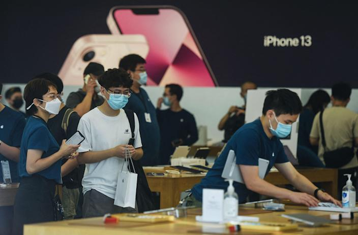 Customers test the newly-launched iPhone 13 mobile phones at an Apple store in Hangzhou, in China's eastern Zhejiang province on September 24, 2021.