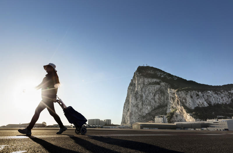A woman walks on the Spanish side of the border between Spain and the British overseas territory of Gibraltar. (AP Photo/Daniel Ochoa de Olza, File)
