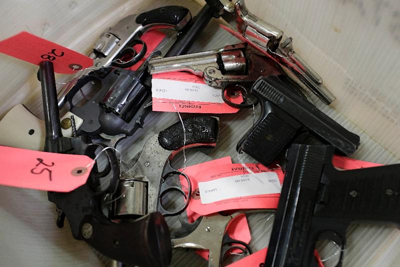 Hand guns are tagged and placed in a bin during a Chicago police gun turn-in event (AFP Photo/Joshua Lott)
