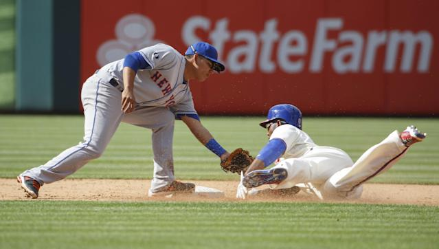 New York Mets shortstop Ruben Tejada, left, tags out Philadelphia Phillies' Domonic Brown, right, for trying to steal second base during the fifth inning of a baseball game, Saturday, May 31, 2014, in Philadelphia. The play was originally ruled safe but was overturned on a replay review. (AP Photo/Chris Szagola)