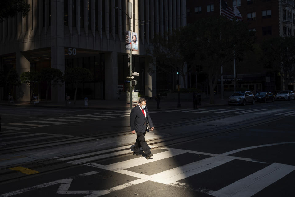 A worker crosses an intersection in San Francisco's financial district mid-afternoon, during what would've been a bustling time before the COVID-19 pandemic, on Wednesday, Oct. 21, 2020. The area remains largely devoid of activity as many employees continue to work from home. (AP Photo/Noah Berger)
