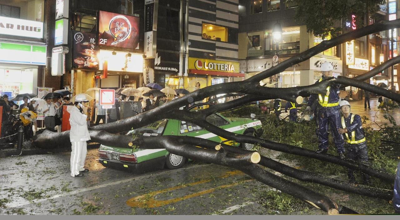 The rear section of a taxi is crushed by a fallen tree in Tokyo on Wednesday Sept. 21, 2011 as powerful Typhoon Roke barreled across central Japan with heavy rains and sustained winds of up to 100 mph (162 kph). (AP Photo/Kyodo News) JAPAN OUT, MANDATORY CREDIT, NO LICENSING IN CHINA, FRANCE, HONG KONG, JAPAN AND SOUTH KOREA