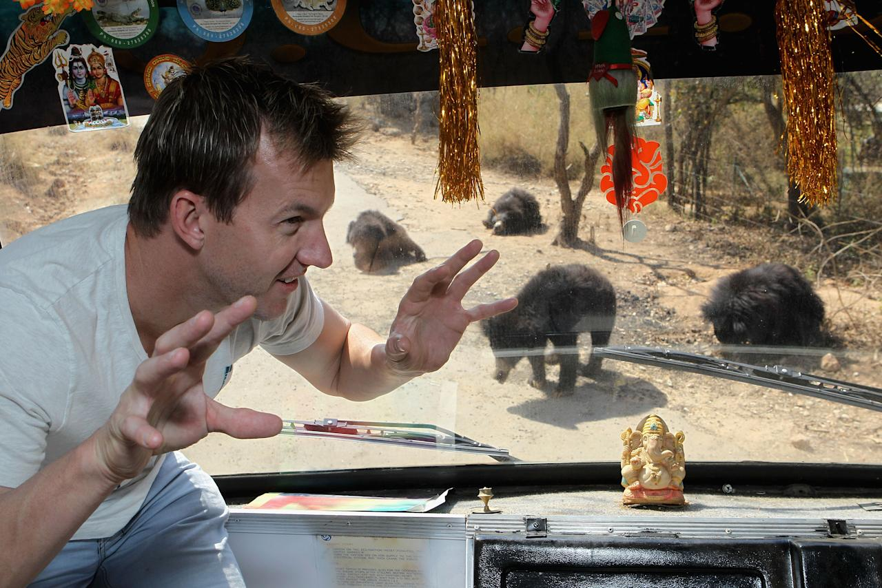 BANGALORE, INDIA - MARCH 12:  Brett Lee of Australia watches some sloth bears through the window of a safari bus during a visit to the Bannerghatta Biological Park on March 12, 2011 in Bangalore, India.  (Photo by Hamish Blair/Getty Images)