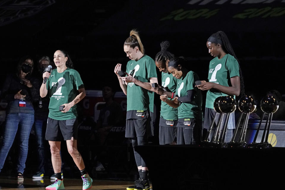 Seattle Storm's Sue Bird, left, speaks to fans as teammates Breanna Stewart, Jewell Loyd, Jordin Canada and Ezi Magbegor eye their new championship rings during a brief ceremony before a WNBA basketball game against the Las Vegas Aces, Saturday, May 15, 2021, in Everett, Wash. (AP Photo/Elaine Thompson)