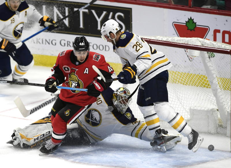 Ottawa Senators center Jean-Gabriel Pageau (44) turns to skate out of the crease as the puck crosses the goal line in front of Buffalo Sabres goaltender Carter Hutton (40) and center Zemgus Girgensons (28) during the second period of an NHL hockey game, Tuesday, Feb. 18, 2020 in Ottawa, Ontario. (Justin Tang/the Canadian Press via AP)