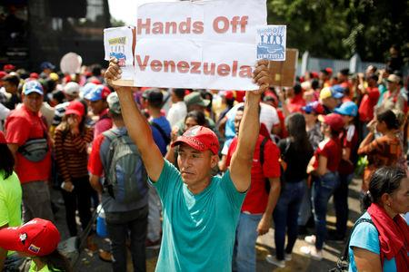FILE PHOTO: A supporter of Venezuela's President Nicolas Maduro holds a banner during a rally in support of him in Urena, Venezuela, February 11, 2019. REUTERS/Marco Bello/File Photo