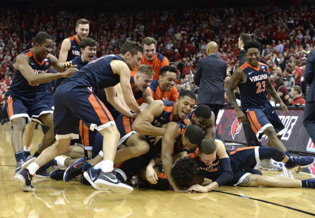 "Teammates pile onto Virginia guard <a class=""link rapid-noclick-resp"" href=""/ncaab/players/136061/"" data-ylk=""slk:De'Andre Hunter"">De'Andre Hunter</a> (12) following his winning three-point basket at the buzzer to defeat Louisville in an NCAA college basketball game, Thursday, March 1, 2018, in Louisville, Ky. (AP Photo/Timothy D. Easley)"