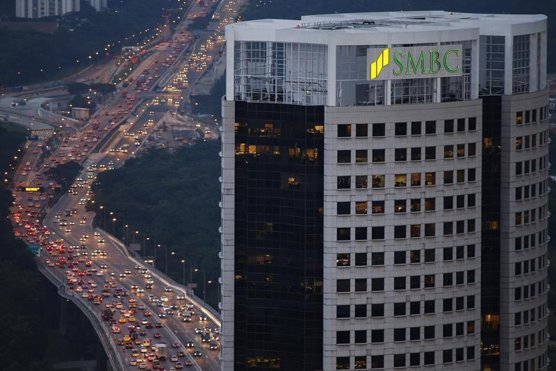 Office workers are seen at their desks in a building housing the Sumitomo Mitsui Banking Corporation offices in Singapore
