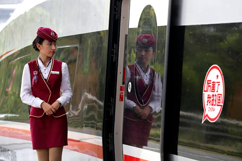 """In this Monday, Oct. 16, 2017, photo, an attendee waits for passengers to board the Fuxing, China's latest high speed train with a sticker reads """"Incredible, my country"""" parked at Hongqiao Railway Station in Shanghai, China. A spokesman for China's ruling Communist Party on Tuesday promised Beijing will open its markets further and tried to reassure foreign companies amid mounting U.S. and European trade complaints. (AP Photo/Andy Wong)"""