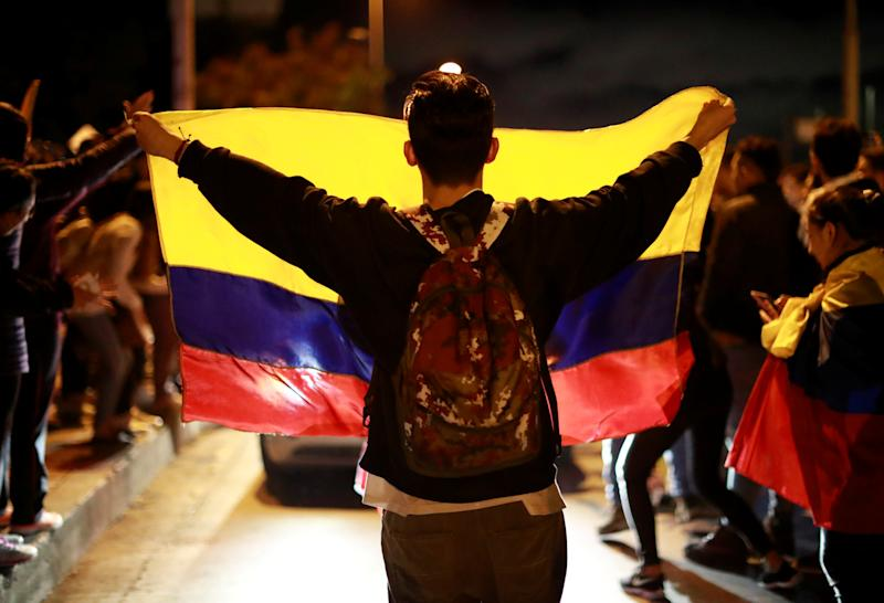 A demonstrator displays a Colombian national flag during a protest as a national strike continues in Bogota, Colombia November 27, 2019. REUTERS/Carlos Jasso