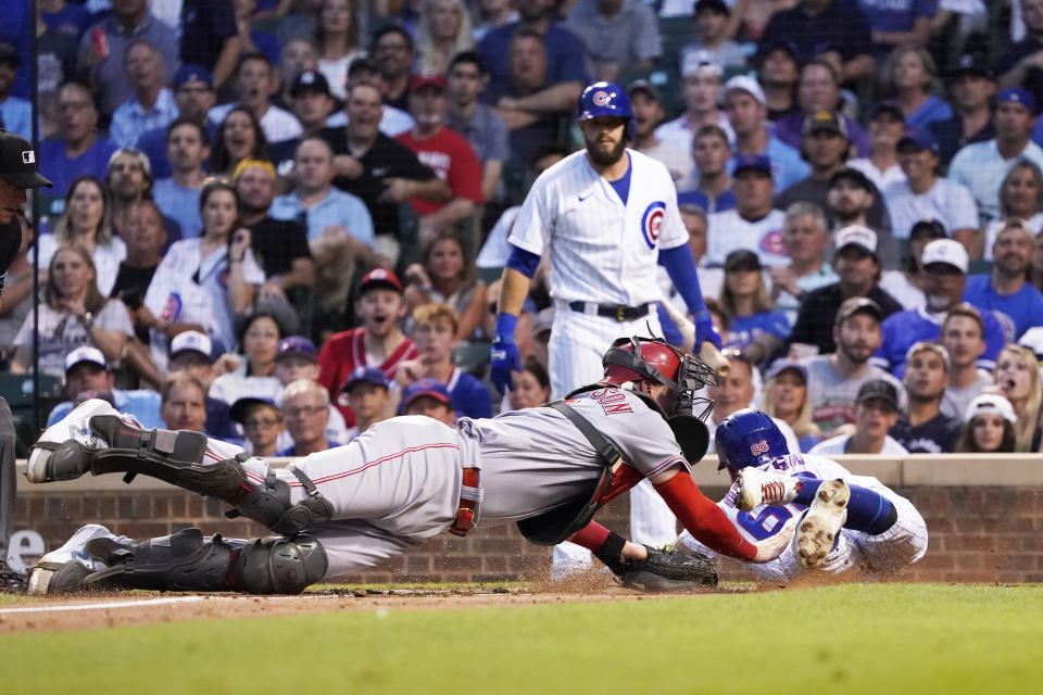 Cincinnati Reds catcher Tyler Stephenson, left, tags out Chicago Cubs' Rafael Ortega at home during the third inning of a baseball game Tuesday, July 27, 2021, in Chicago. (AP Photo/David Banks)