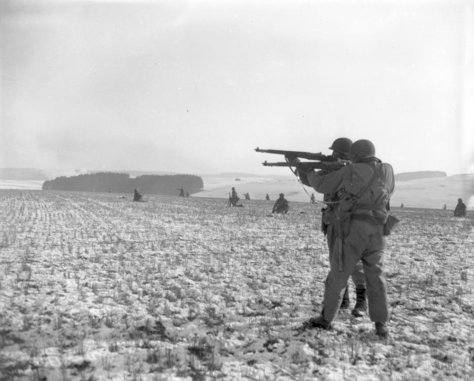 """FILE - In this Dec. 27, 1944, file photo, American infantrymen of the 4th Armored Division fire at German troops, in an advance to relieve pressure on surrounded U.S. airborne units, near Bastogne, Belgium. In 2020, the world marked the 75th anniversary of the end of World War II. Sterling Publishing, in cooperation with The Associated Press, released an illustrated book called """"Victory: World War II In Real Time,"""" filled with original AP dispatches from the time to mark the occasion and scores of original news photos. (U.S. Army via AP)"""