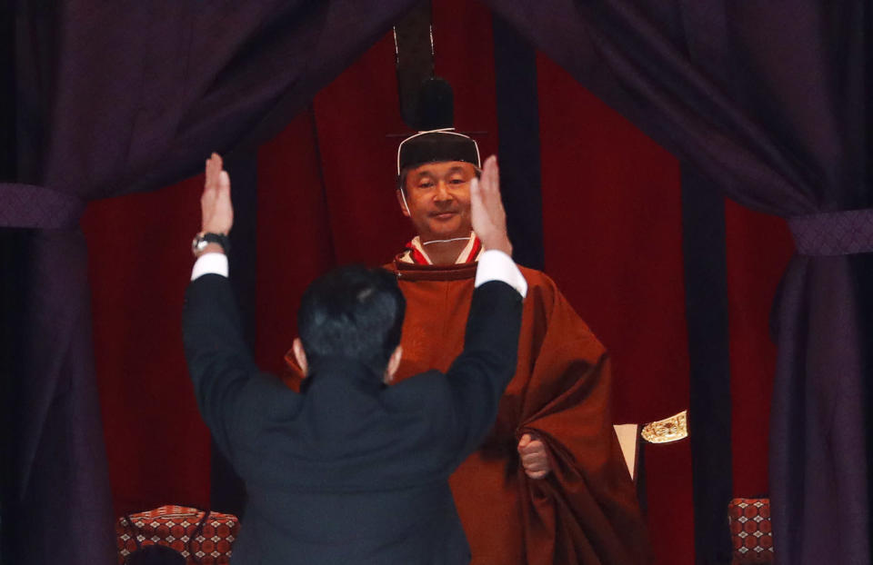 """Japan's Prime Minister Shinzo Abe raises his hands as he shouts """"banzai"""" or cheers in front of Emperor Naruhito during a ceremony to proclaim Emperor Naruhito's enthronement to the world, called Sokuirei-Seiden-no-gi, at the Imperial Palace in Tokyo, Japan, Tuesday, Oct. 22, 2019. (Issei Kato/Pool Photo via AP)"""