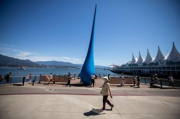 People are pictured waiting in line outside of Canada Place for their COVID-19 vaccination in Vancouver, British Columbia on Monday June 21, 2021. (Ben Nelms/CBC - image credit)