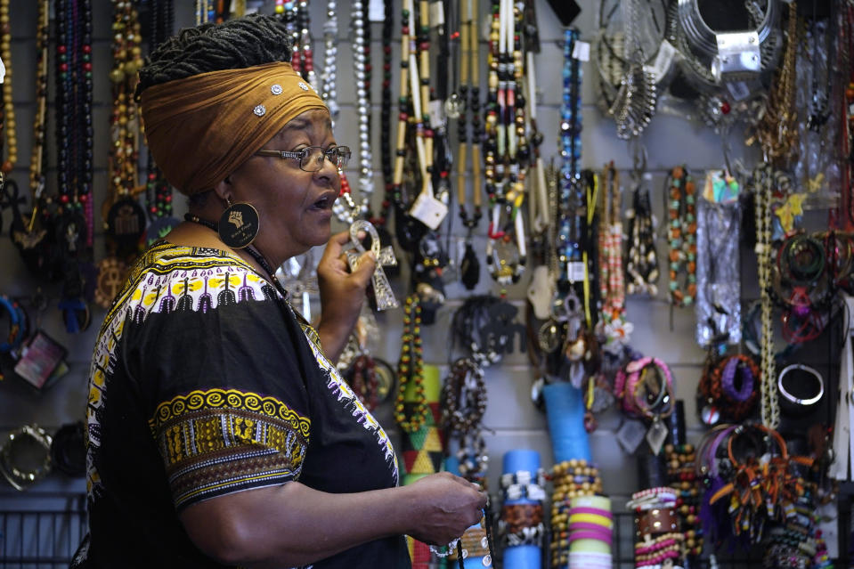 Billie Parker, owner of the Black Wall Street Market, displays some of the items she has for sale in Tulsa, Okla., on Saturday, April 10, 2021. Her establishment, in an underdeveloped and underserved section of the city, is a far cry from the booming city within a city that was Greenwood, with its Black grocers, shopkeepers, doctors, lawyers, newspaper publishers and other businessmen and women. But Parker thought it was important to lay claim to the name and its legacy. (AP Photo/Sue Ogrocki)