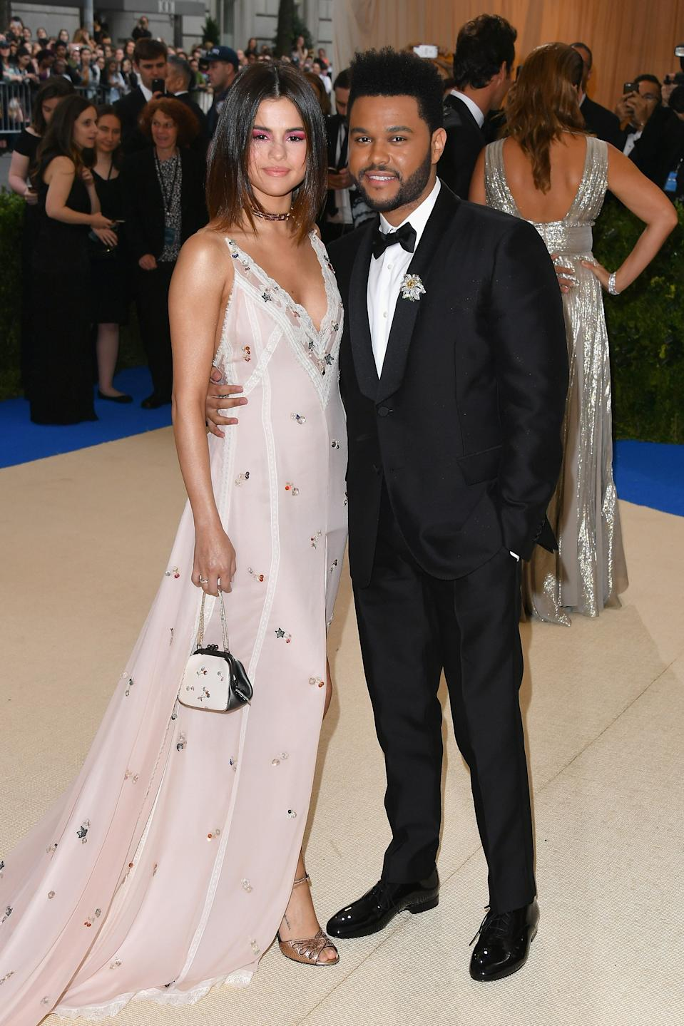 """<h1 class=""""title"""">Selena Gomez in Coach and Tiffany jewelry and The Weeknd in a Valentino tuxedo</h1><cite class=""""credit"""">Photo: Getty Images</cite>"""