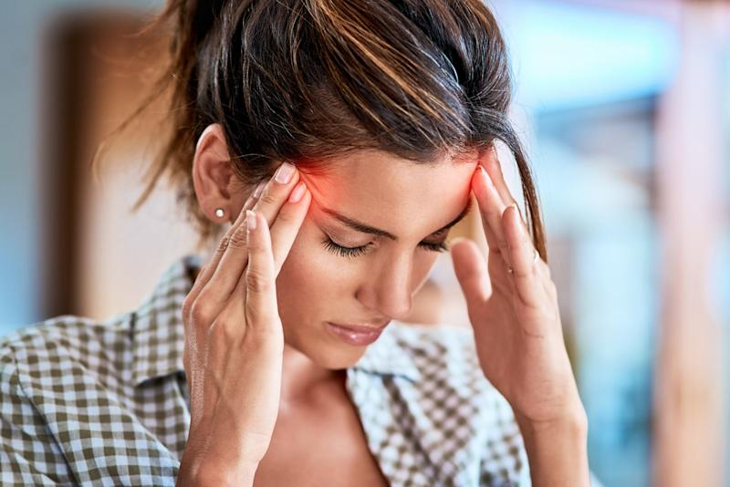 Shot of a uncomfortable looking woman holding her head in discomfort due to pain at home during the day