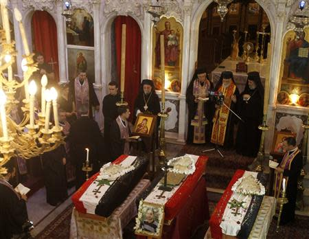 Clerics and other people attend the funeral of three men at Catholic Patriarchate in Damascus September 10, 2013. REUTERS/Khaled al-Hariri