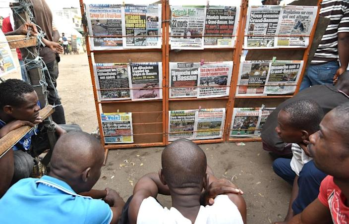 People look at newspapers on March 14, 2016 in Abidjan, a day after gunmen attacked the Ivory Coast resort town of Grand-Bassam (AFP Photo/Sia Kambou)